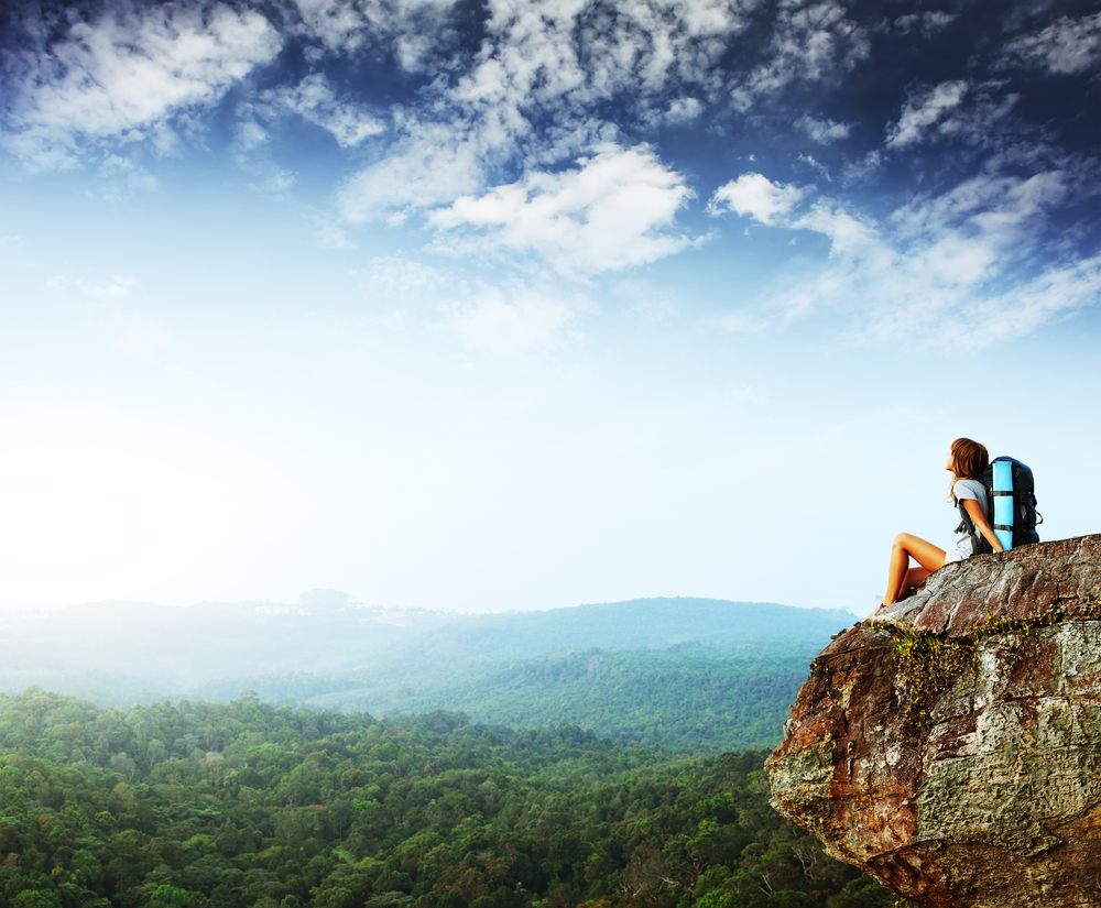 Young woman with backpack sitting on cliff and looking to a sky.