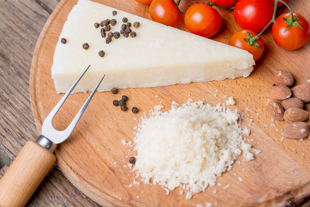 Grated pecorino cheese on wooden cutting board with tomatoes, selective focus.