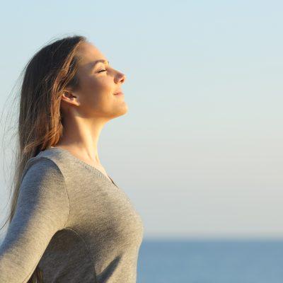 Woman breaths fresh air on the beach
