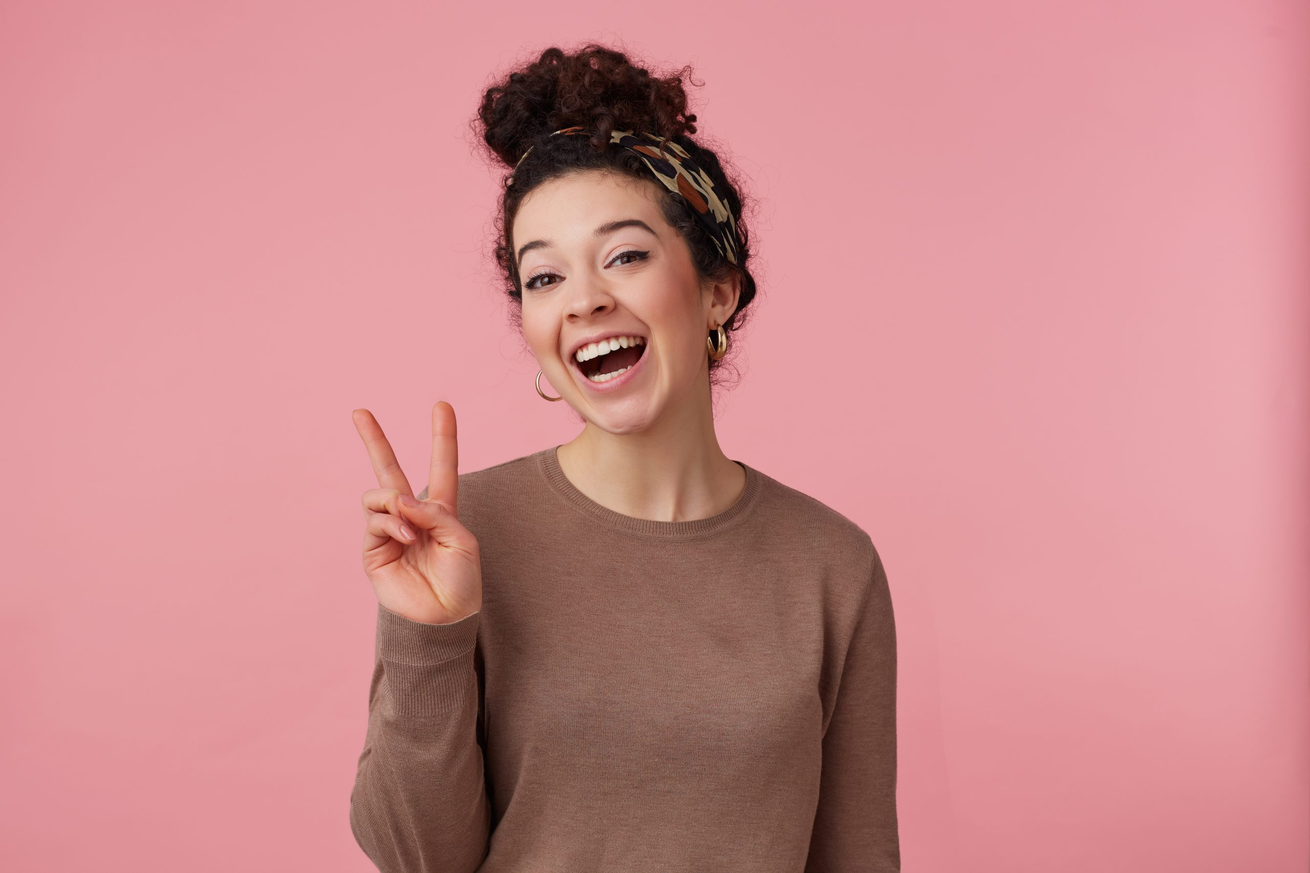 Cheerful woman, beautiful girl with dark curly hair bun. Wearing headband, earrings and brown sweater. Has make up. Showing peace sign. Watching at the camera isolated over pastel pink background